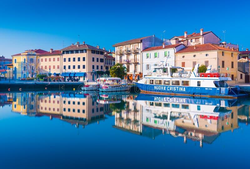 Grado, Italie : Les bâtiments résidentiels et les bateaux colorés sont miroir reflété en eau de mer photos stock