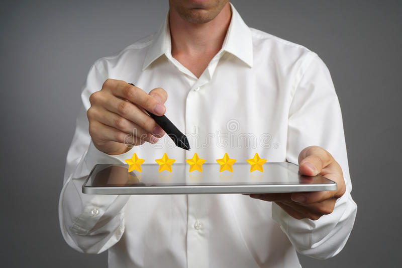 Grado o graduación, concepto de cinco estrellas de la evaluación comparativa El hombre con la tableta evalúa el servicio, hotel,  imágenes de archivo libres de regalías