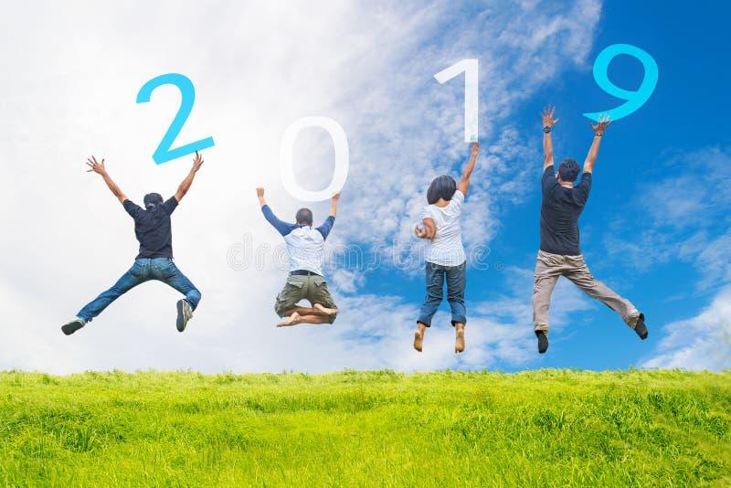 Graduação de salto feliz do trabalho da equipe dos amigos e das felicitações dos povos adultos no ano novo feliz 2019 Chá do negó foto de stock royalty free