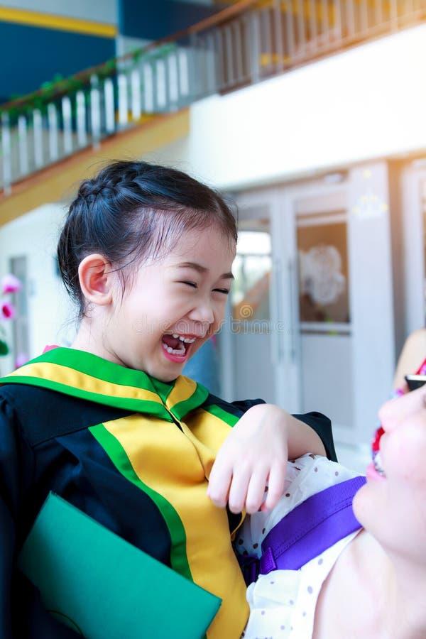 Graduação do jardim de infância Mamã feliz e filha que sorriem felizmente foto de stock