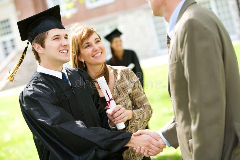 Graduação: A mãe está pelo filho com orgulho fotografia de stock royalty free