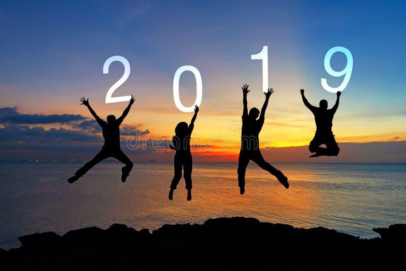 Graduación de salto de la enhorabuena del trabajo en equipo feliz del negocio de la silueta en la Feliz Año Nuevo 2019 La gente d imagenes de archivo