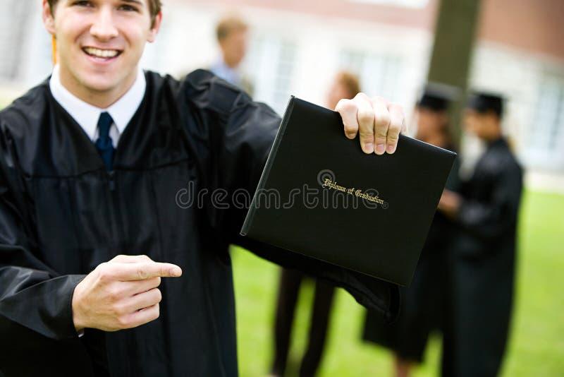 Graduación: Estudiante emocionado Points en el diploma foto de archivo libre de regalías