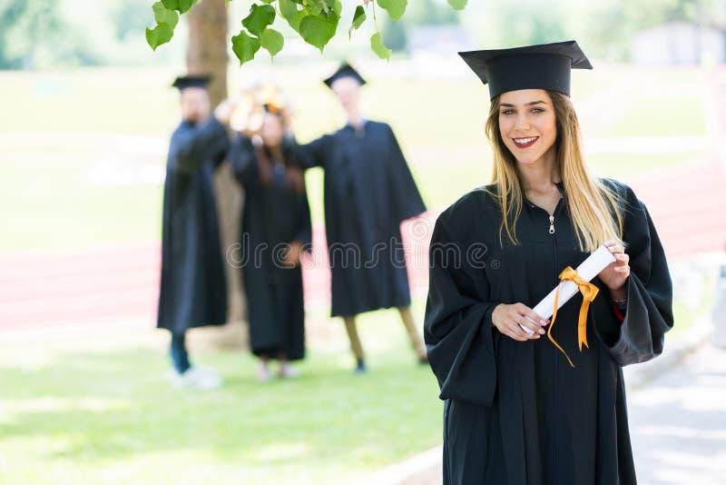 Graduación: Estudiante Standing With Diploma con los amigos detrás imagen de archivo libre de regalías