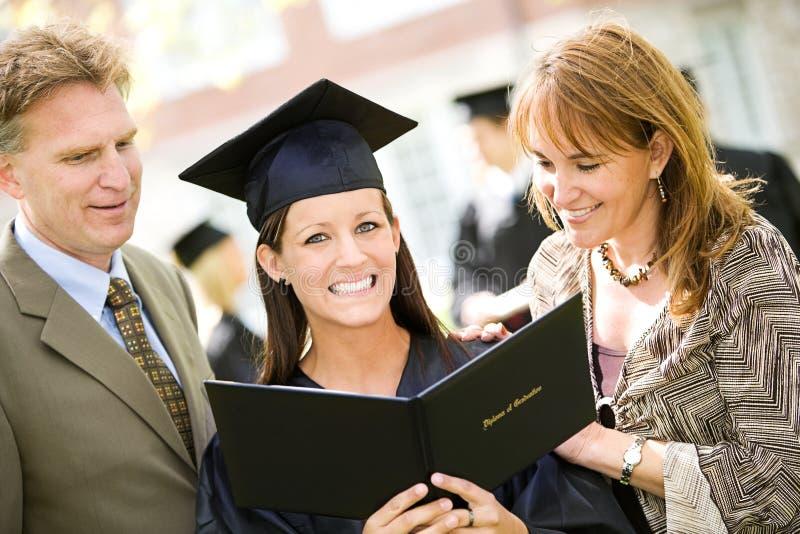 Graduación: Familia orgullosa con la hija graduada fotografía de archivo