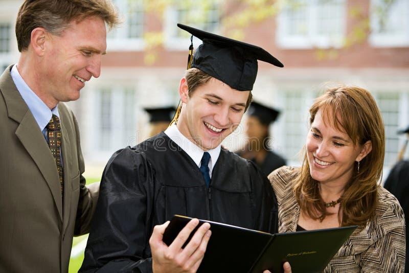 Graduación: La familia orgullosa admira el diploma fotografía de archivo libre de regalías