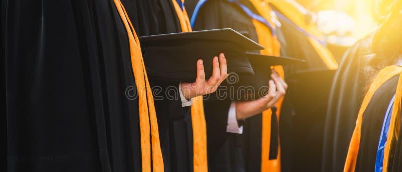 Graduado ascendente cercano que sostiene un sombrero Educaci?n del ?xito del concepto en universidad con el espacio de la copia G foto de archivo libre de regalías