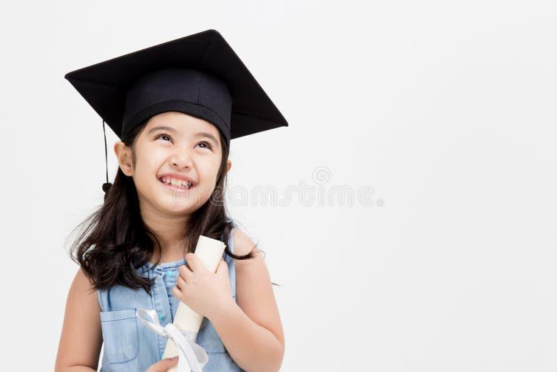 Graduado asiático feliz da criança da escola no tampão da graduação imagem de stock
