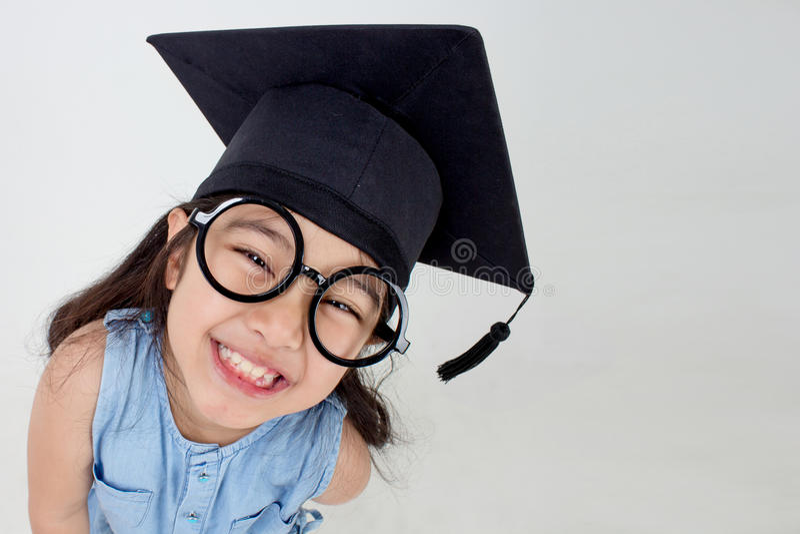 Graduado asiático feliz da criança da escola no tampão da graduação fotos de stock