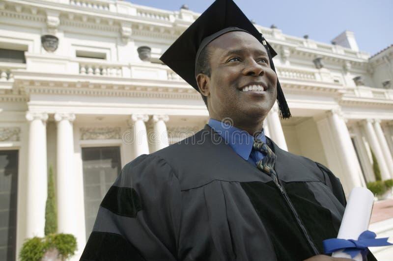 Graduado con el diploma fuera de la universidad imagen de archivo