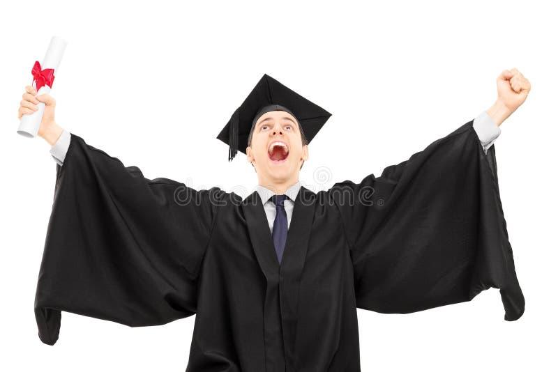 Graduado de faculdade extático que guarda um diploma e que gesticula o happi fotografia de stock