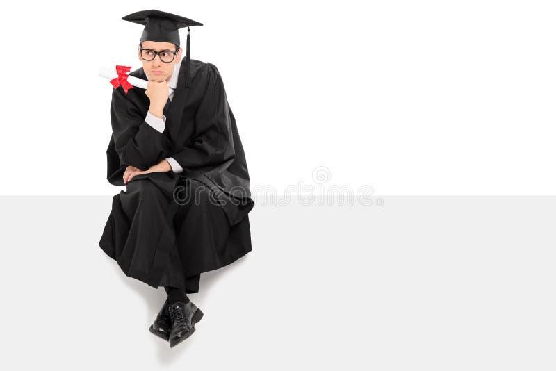 Graduado de faculdade pensativo que senta-se em um painel vazio imagens de stock