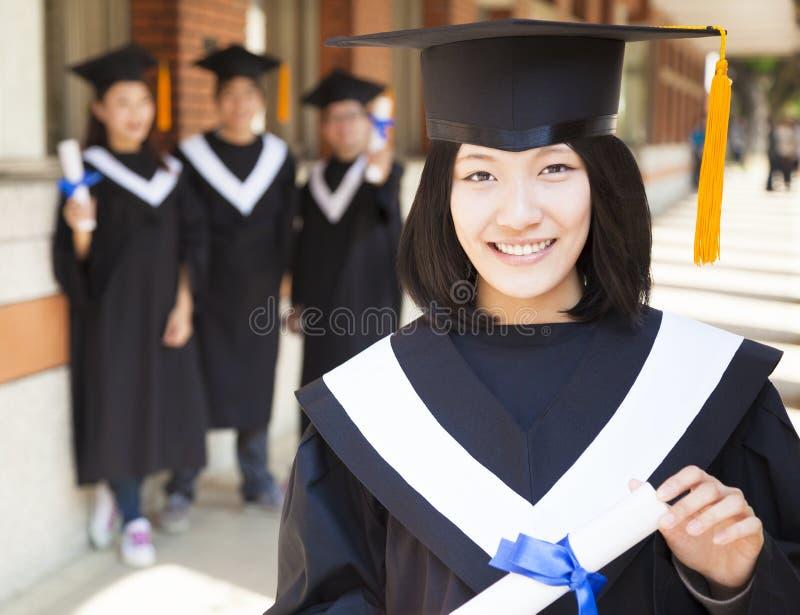 Graduado de universidad bastante femenino que sostiene el diploma fotos de archivo libres de regalías
