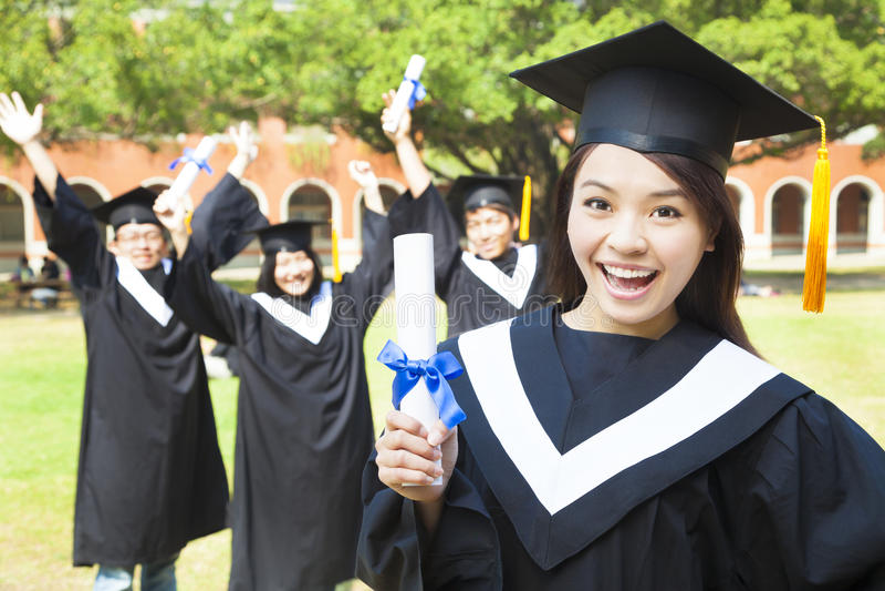 Graduado de universidad feliz que sostiene un diploma con los amigos imagenes de archivo