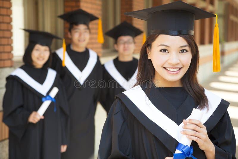 Graduado de universidad hermoso que sostiene el diploma con los compañeros de clase imágenes de archivo libres de regalías
