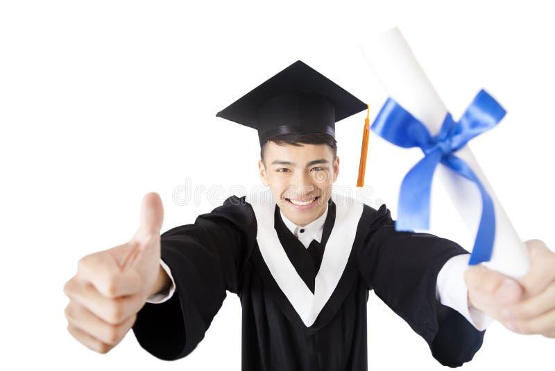 Graduado de universidad masculino joven con el pulgar para arriba imagenes de archivo