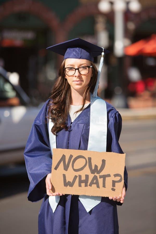 Graduado de universidad que se coloca con la muestra fotografía de archivo