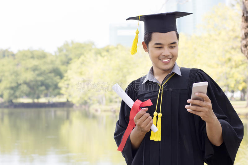 Graduado do estudante que guarda o telefone esperto fotos de stock