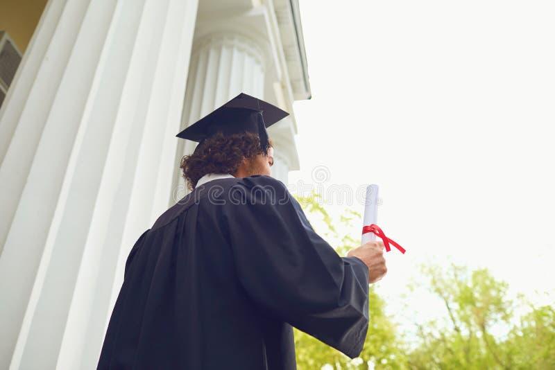 Graduado feliz com diploma à disposição no fundo de universidade fotos de stock royalty free