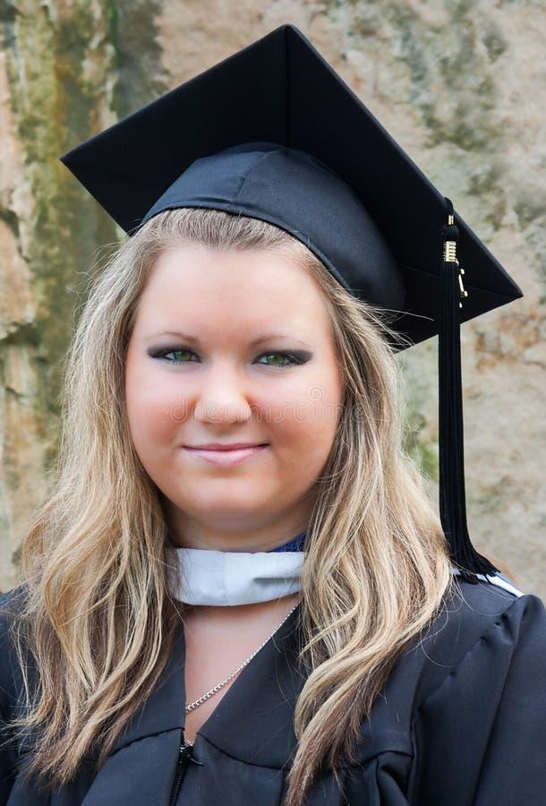 Graduado femenino de la universidad en casquillo y vestido foto de archivo