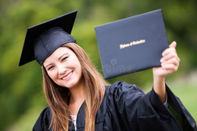 Graduado: Mulher que sustenta orgulhosamente o diploma fotografia de stock royalty free