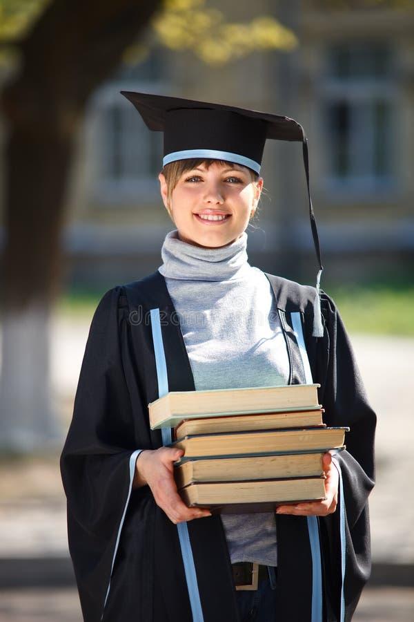 Graduado novo da fêmea com uma pilha de livros imagem de stock