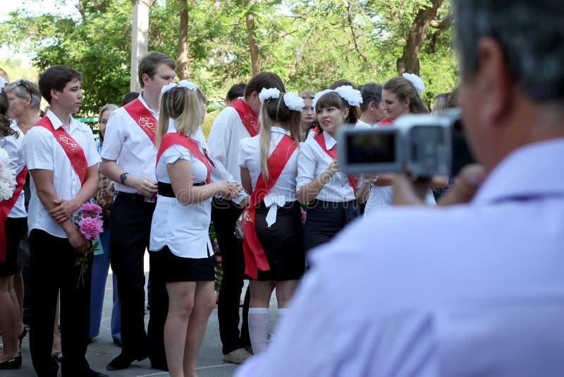 Graduados da escola na frente das câmeras foto de stock