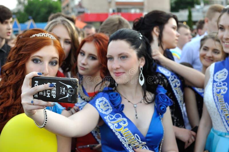 Graduados das escolas diferentes que tomam o selfie em uma parada da celebração fotos de stock royalty free