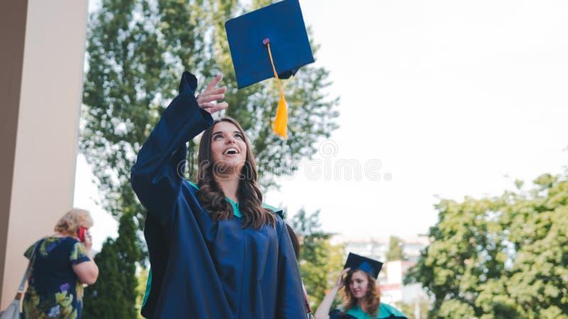 Graduados de la universidad que lanzan los sombreros de la graduación en el aire Grupo de graduados felices en vestidos académico fotografía de archivo