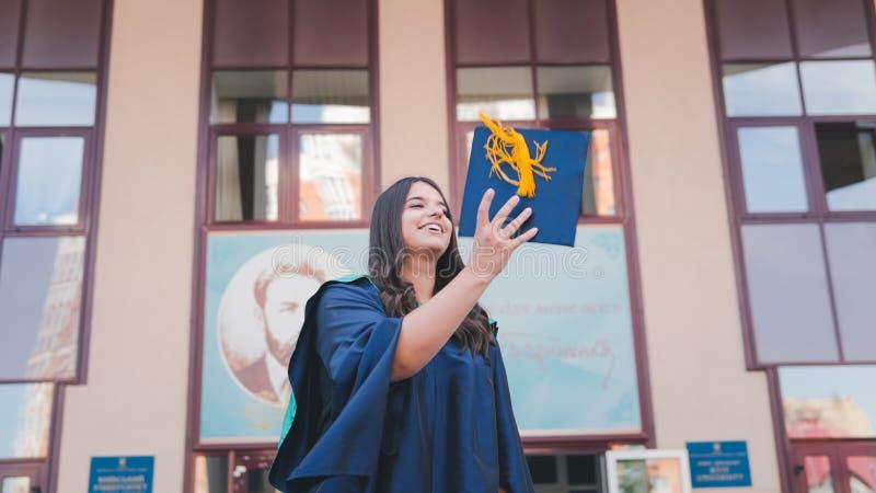 Graduados de la universidad que lanzan los sombreros de la graduación en el aire Grupo de graduados felices en vestidos académico fotografía de archivo libre de regalías