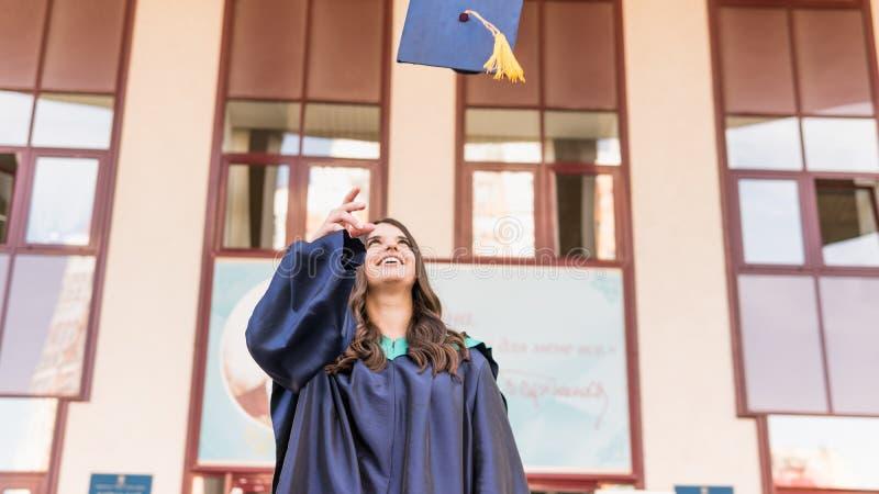 Graduados de la universidad que lanzan los sombreros de la graduación en el aire Grupo de graduados felices en vestidos académico fotos de archivo libres de regalías