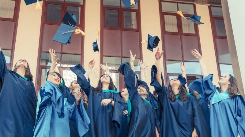 Graduados de la universidad que lanzan los sombreros de la graduación en el aire Grupo de graduados felices en vestidos académico imagen de archivo libre de regalías