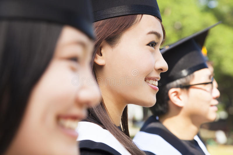 Graduados de una universidad alegres del grupo en la graduación foto de archivo