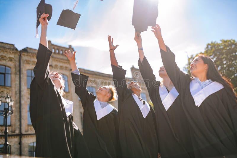 Graduados que dizem adeus a sua vida da universidade imagem de stock royalty free