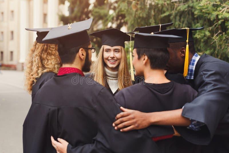 Graduados que têm o abraço do grupo no dia de graduação imagem de stock royalty free