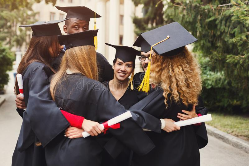 Graduados que tienen abrazo del grupo el día de graduación fotos de archivo