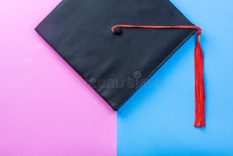 Graduate cap or mortarboard with red tassel on color rubber foam sheet. Graduate cap or mortarboard on pink blue rubber foam sheet background, colorful design royalty free stock images