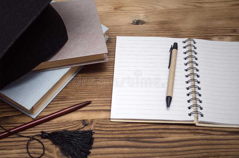 Education background. Graduate cap, stack of books and workbook with blank pages on the wooden school desk with copy space stock image