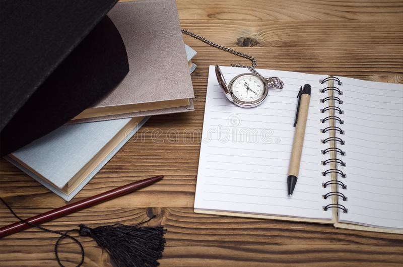 Education background. Graduate cap, stack of books and workbook with blank pages on the wooden school desk with copy space stock photo