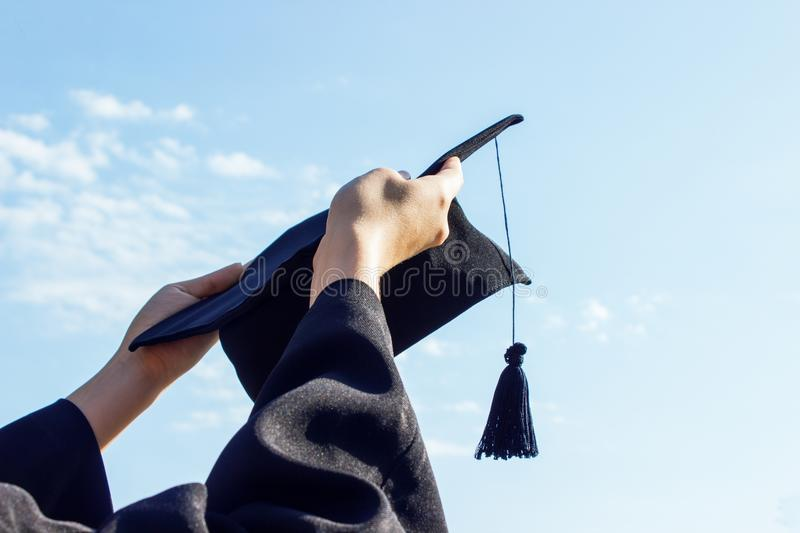 Graduate celebrating with cap in her hand,feeling so proud and happiness in Commencement day.  stock images