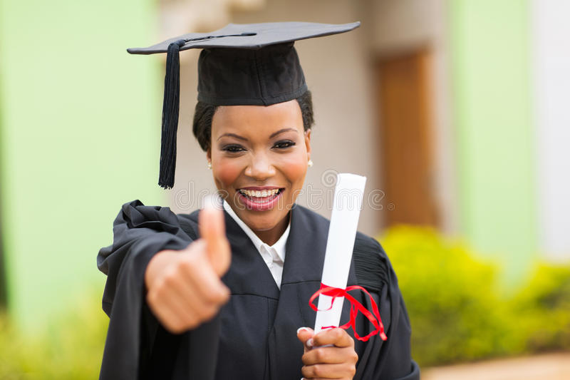 Graduate giving thumb up stock photography