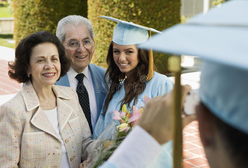 Graduate and grandparents having photograph taken outside stock photos