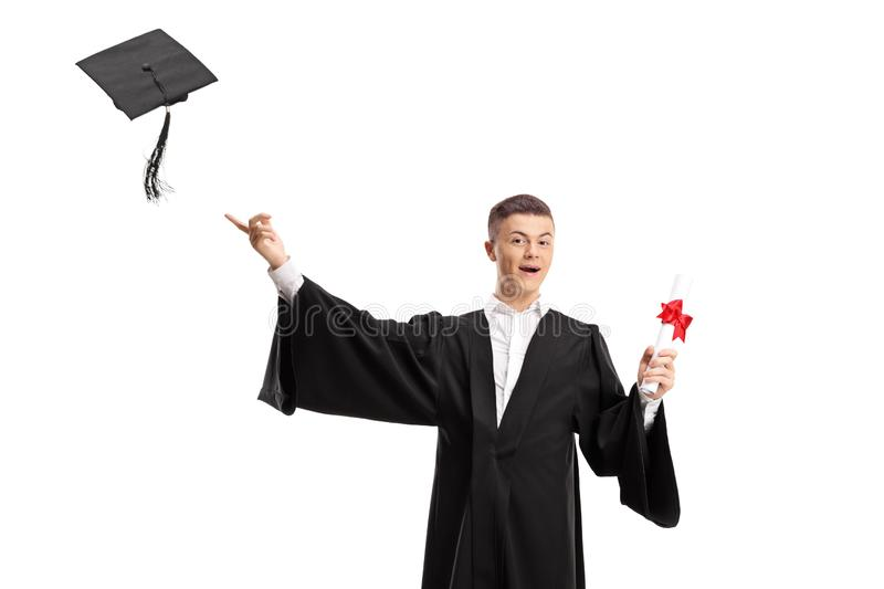 Graduate male student holding a diploma and throwing a graduation hat royalty free stock image