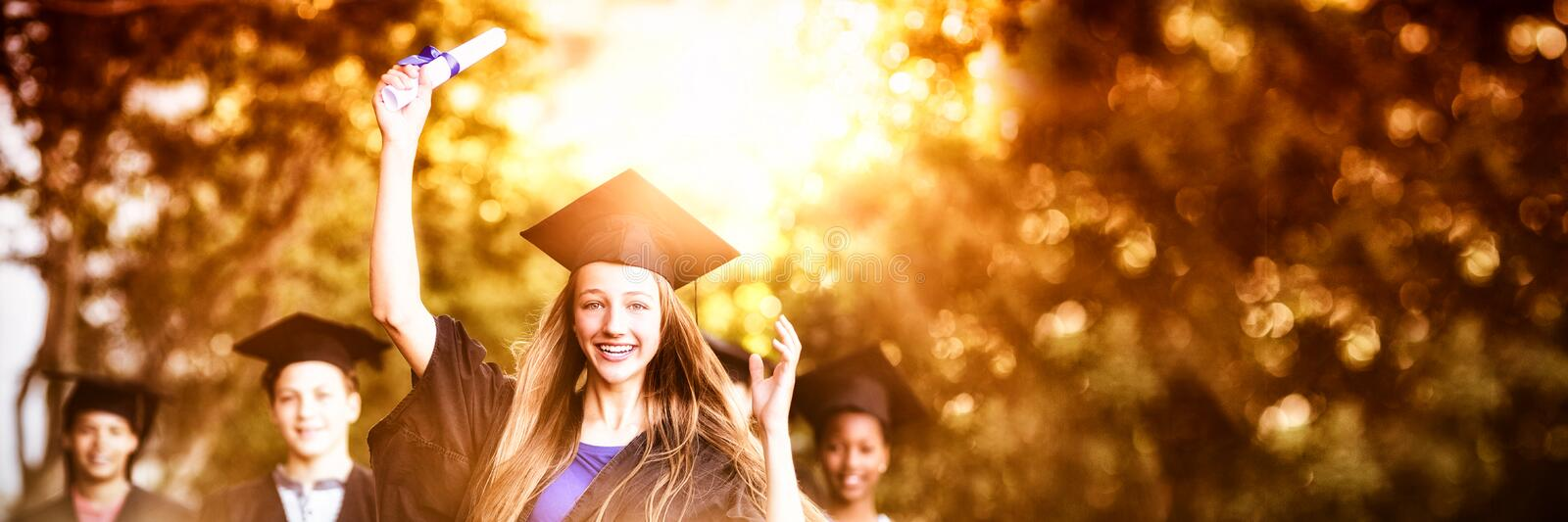 Graduate school kids standing with degree scroll in campus stock photography