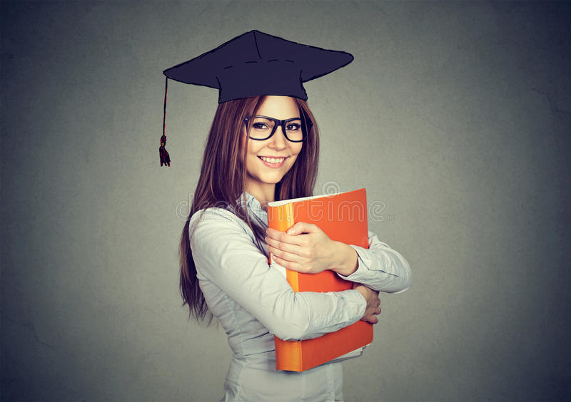 Graduate student woman in cap gown with folder looking at camera stock photos
