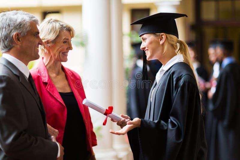 Graduate talking parents stock photography
