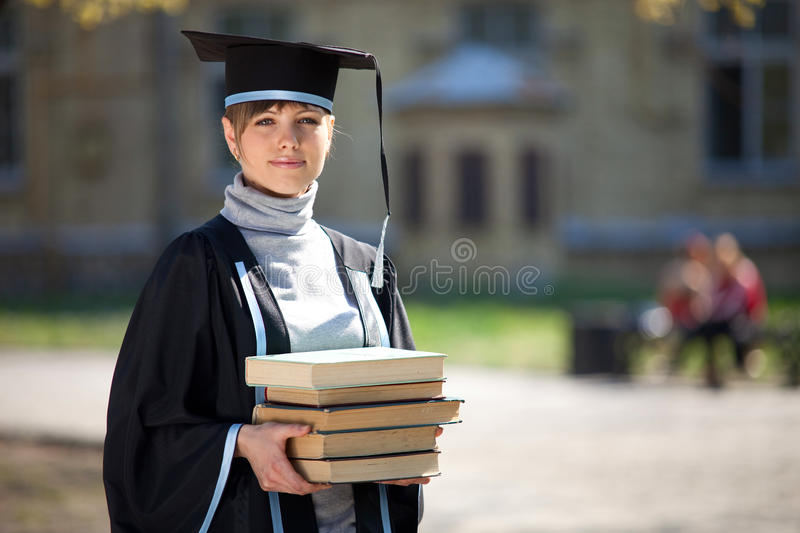 Graduate of university with books stock photography