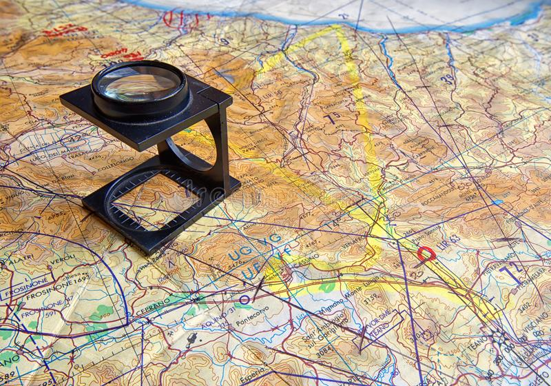 Folding magnifier on flight map. A graduated folding magnifier, set up on a military flight map, featuring an area of Italy stock photography