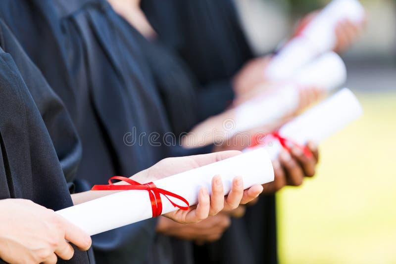 Graduates with diplomas. royalty free stock photo