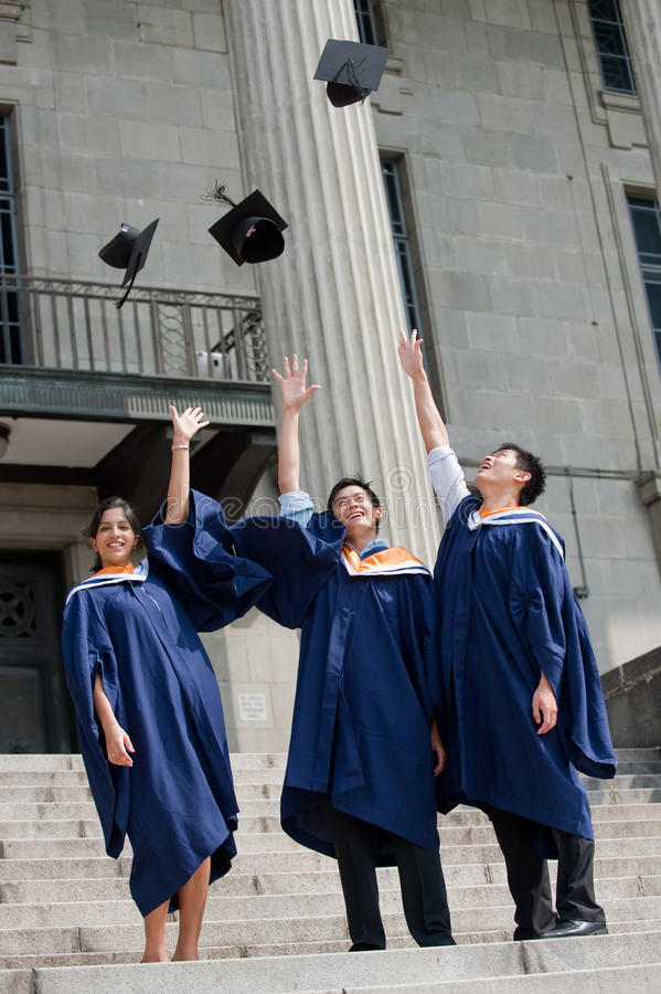 Graduates Hat Toss. A group of graduates toss their mortar boards into the air stock images